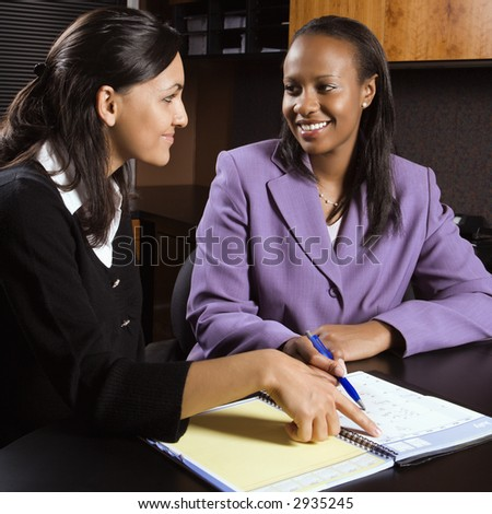 African-American and Indian young adult smiling business women working together in office. - stock photo