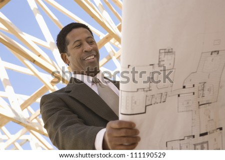 African American architect examining a blueprint at a construction site - stock photo