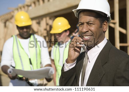 African American architect phoning at a construction site - stock photo