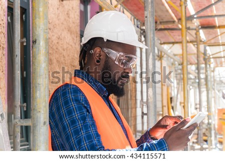 African american architect wearing safety equipment (glasses, helmet and jacket) checking documents on tablet computer at construction site - stock photo