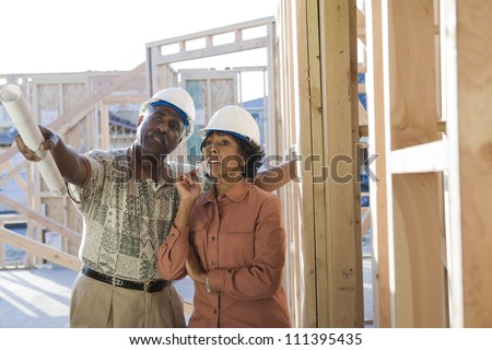 African American architects with blueprint discussing plans on site - stock photo