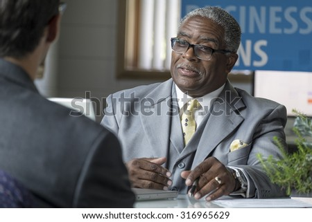 African American Banker at his desk helping his client with a business loan - stock photo