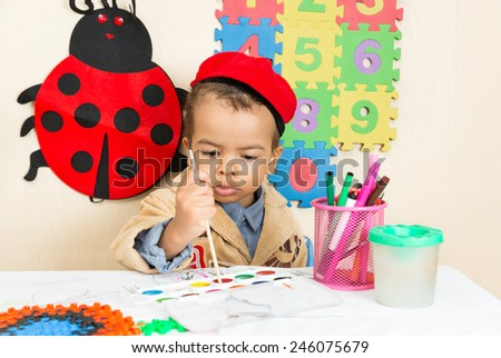 African American black boy drawing with colorful pencils in preschool at table in kindergarten - stock photo
