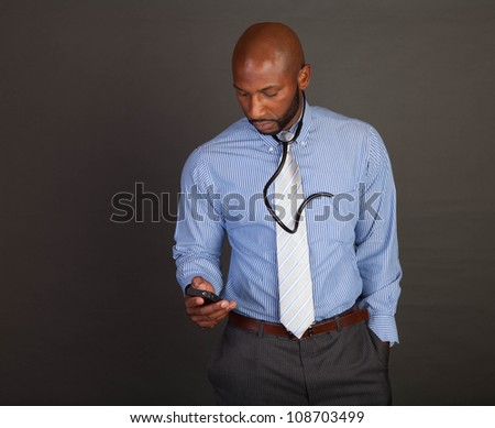 African American / Black doctor checking his cell phone