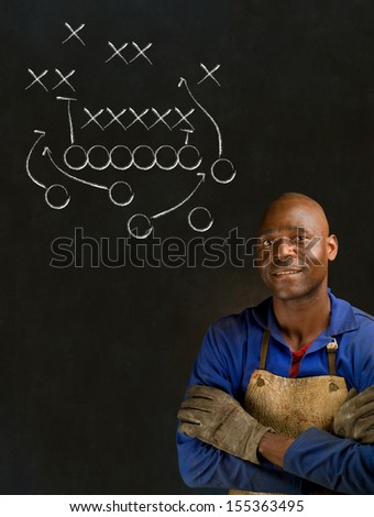African American black man industrial worker with chalk game plan on a blackboard background - stock photo