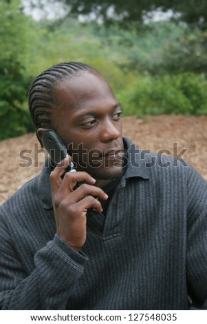 African American Black man outside talking on his cell phone with a thoughtful expression - stock photo