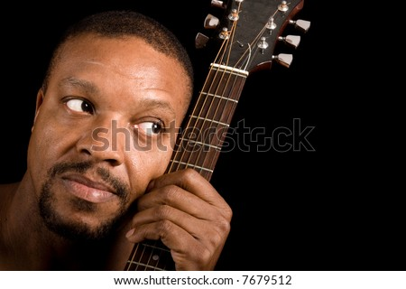 african american blues singer with guitar, looking into empty copy space - stock photo