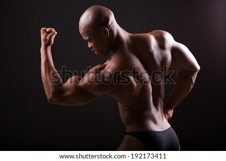 african american bodybuilder showing muscles on black background - stock photo