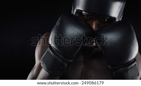 African american boxer wearing protective gear against black background. Young man exercising boxing. - stock photo