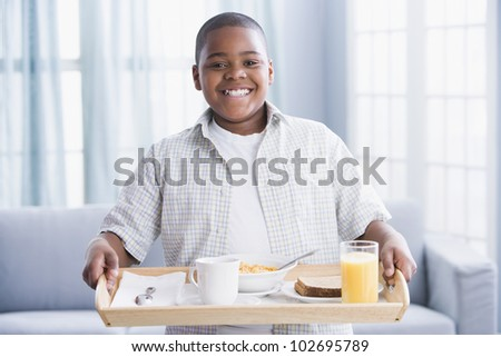 African American boy carrying breakfast tray - stock photo