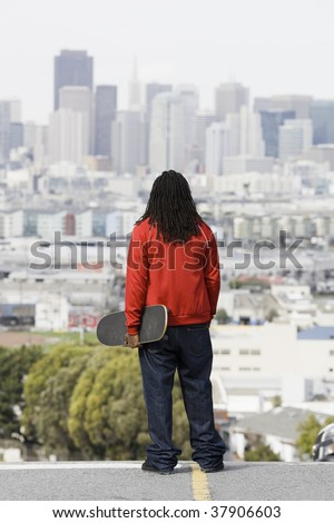 African American Boy Holding Skateboard Looking at City View - stock photo