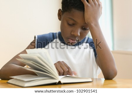 African American boy reading book - stock photo