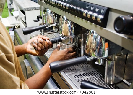African American brewing some coffee at the espresso machine in a coffee shop