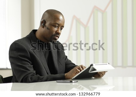 African American business man on his blue tooth using tablet. - stock photo