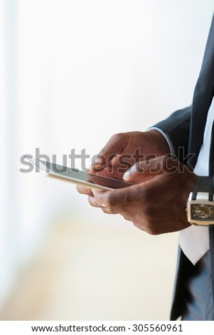 African american business man using a tactile tablet over white background - Black people - stock photo