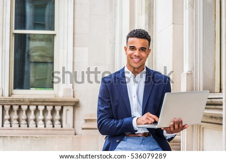 African American Business Man working in New York. Student wearing black blazer, sitting inside vintage office building on campus, reading, studying on laptop computer, smiling. Color filtered effect.