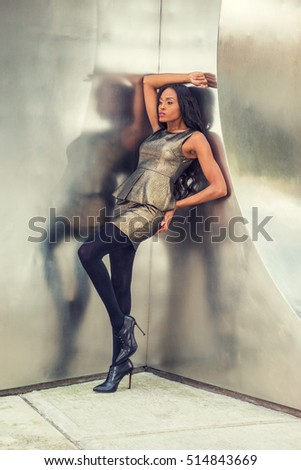 African American Business Woman Fashion in New York. Lady wearing metal crystal sleeveless mini dress top, skit suit, black leggings, high heels, stands against silver metal wall, relaxing, thinking.