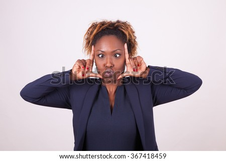 African American business woman grimacing making frame gesture with her hands, isolated on gray background - stock photo