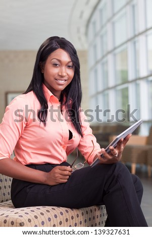 african-american business woman sitting in lobby with computer tablet, looking at camera, smiling - stock photo