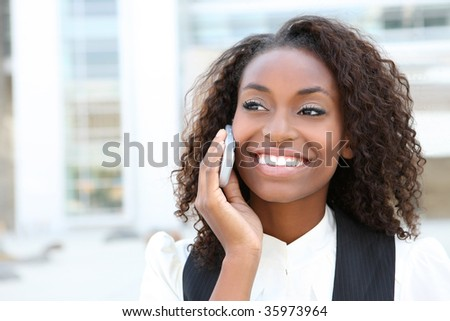 African american business woman talking on a  cell phone in front of an office building - stock photo