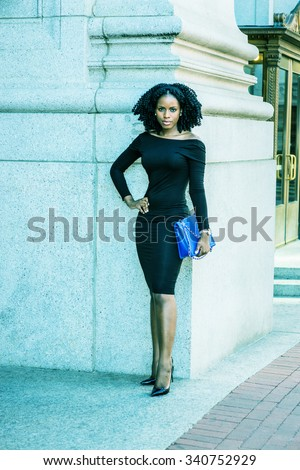 African American Business Woman working in New York. Wearing long sleeve, slim off shoulder dress, carrying blue bag, a black lady with braid hairstyle standing outside. Filtered look with green tint. - stock photo
