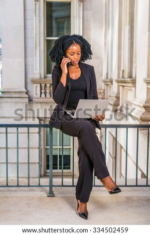 African American Business Woman working in New York. Young black college student with braid hairstyle sitting on railing in vintage style office building, working on laptop computer, calling on phone. - stock photo