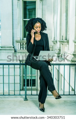 African American Business Woman working in New York. Young black college student with braid hairstyle sitting on railing, working on laptop computer, calling on phone. Filtered look with green tint. - stock photo