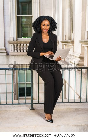 African American Business Woman working in New York. Young black college student with braid hairstyle sitting on railing in vintage style office building, reading, working on laptop computer.