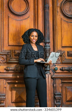 African American Business Woman working in New York. young black female college student with braid hairstyle standing by vintage style office doorway, smiling, reading, working on laptop computer.  - stock photo