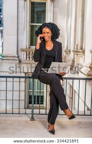African American Business Woman working in New York. Young black lady with braid hairstyle sitting on railing in vintage style office building, smiling, working on laptop computer, making phone call. - stock photo