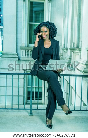 African American Business Woman working in New York. Young black lady with braid hairstyle sitting on railing, smiling, working on laptop computer, making phone call. Filtered look with cyan tint. - stock photo