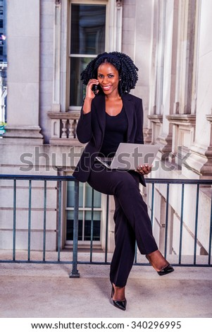 African American Business Woman working in New York. Young black lady with braid hairstyle sitting on railing, smiling, working on laptop computer, making phone call. Filtered look with purple tint. - stock photo