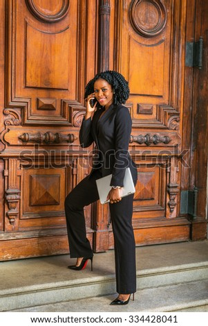 African American Business Woman working in New York. Young black lady with braid hairstyle walking up steps on vintage style office doorway, carrying laptop computer, smiling, calling on cell phone. - stock photo