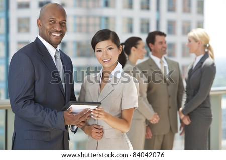 African American businessman and Chinese Asian businesswoman using tablet computer with interracial group of business men & women team. - stock photo