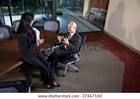African American businessman and female colleague having discussion in boardroom - stock photo