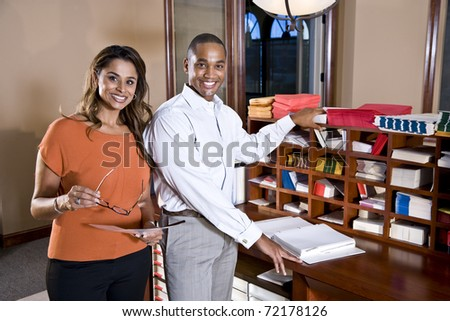 African American businessman and Indian businesswoman working together in office - stock photo