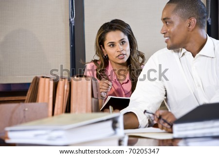 African American businessman and Indian businesswoman working together in office, focus on woman - stock photo