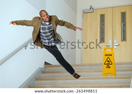 African American businessman falling on stairwell with yellow warning sign on steps - stock photo