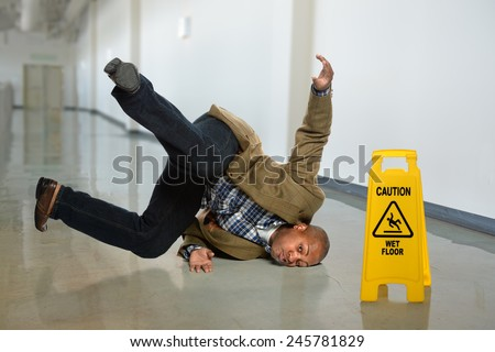 African American businessman falling on wet floor in office - stock photo