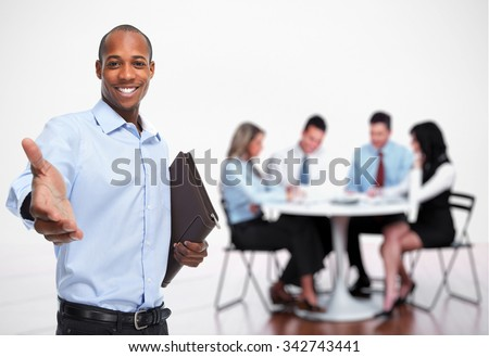 African-American businessman handshake over people group background - stock photo