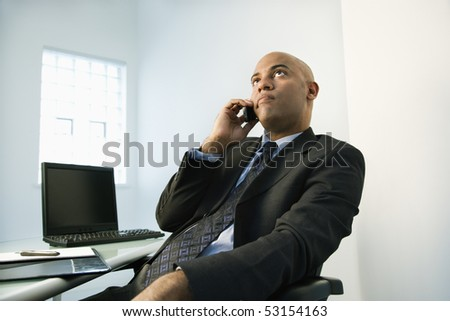 African American businessman holding cellphone to ear looking bored. - stock photo