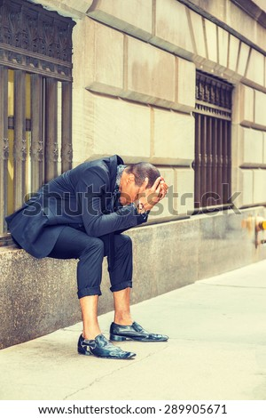 African American businessman in New York. Dressing in black suit, tie, leather shoes, young black guy sitting on window on street, bending back, hands covering head, tired, sad. Instagram effect.  - stock photo