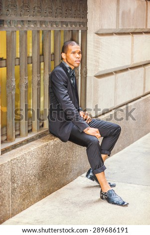 African American businessman in New York. Dressing in suit, tie, leather shoes, a young black guy sitting on vintage style window frame on street, relaxing, thinking, waiting for you. City Life.   - stock photo