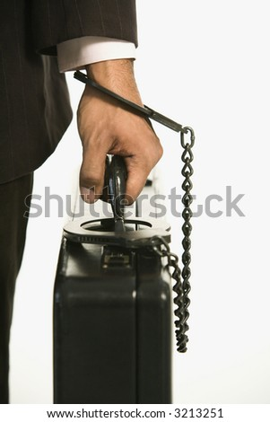 African American businessman in suit handcuffed to briefcase. - stock photo
