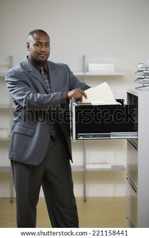 African American businessman looking in file cabinet - stock photo