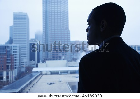 African-American businessman looking out of a window at the city. Horizontal shot. - stock photo