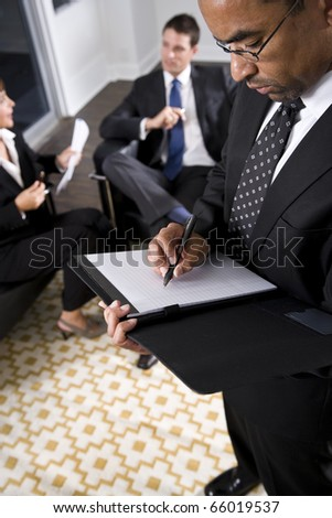 African American businessman, 40, making notes, co-workers conversing in background