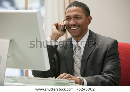 African American businessman on the phone sitting at the computer in his office - stock photo
