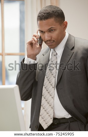 African American businessman on the phone standing in his office - stock photo