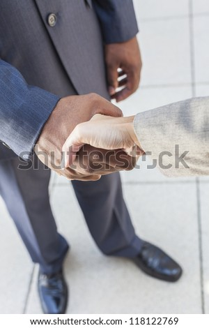 African American businessman or man shaking hands with a businesswoman or woman caucasian female colleague making a business deal - stock photo